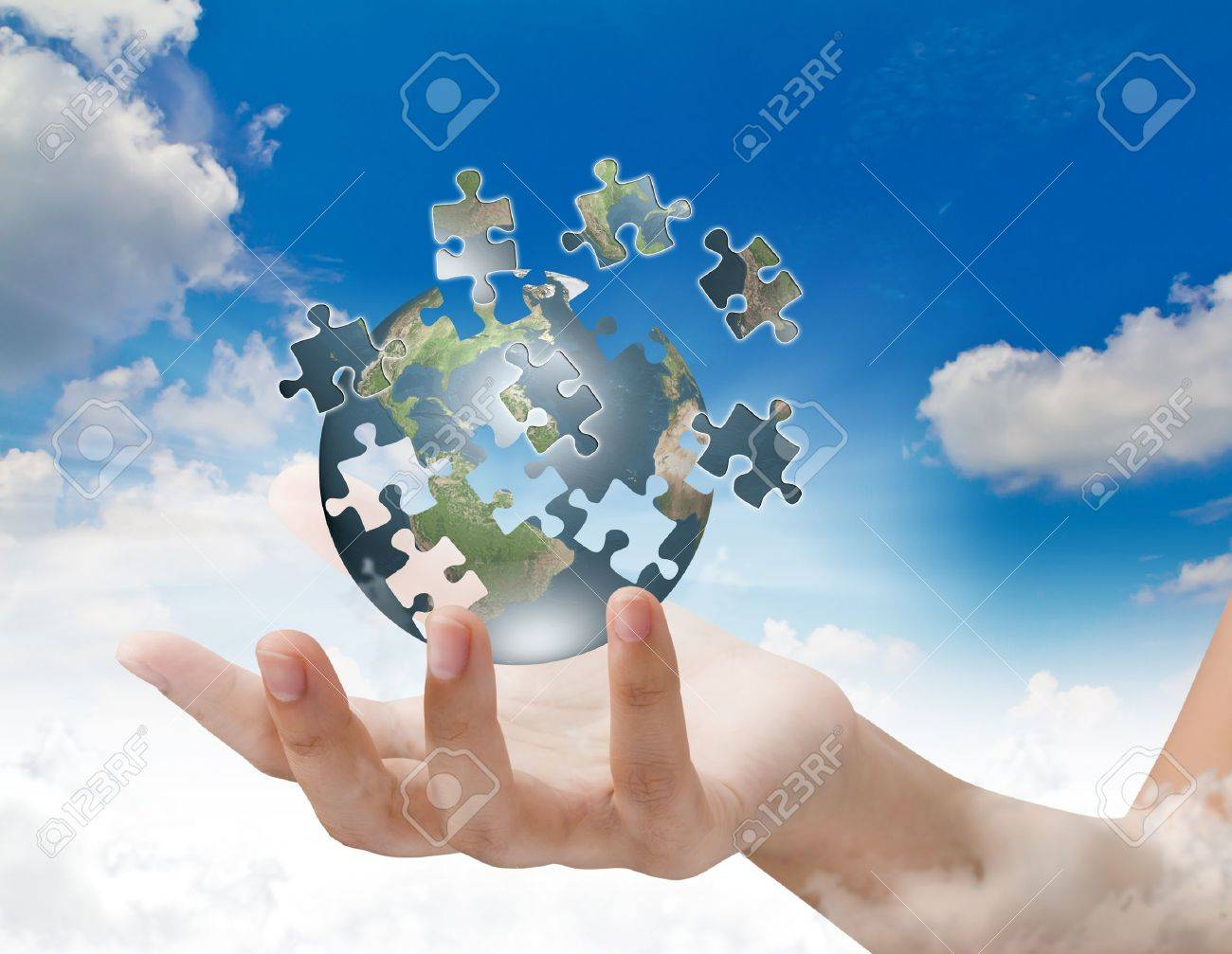 Business concept with a hand building puzzle globe Stock Photo - 11425161