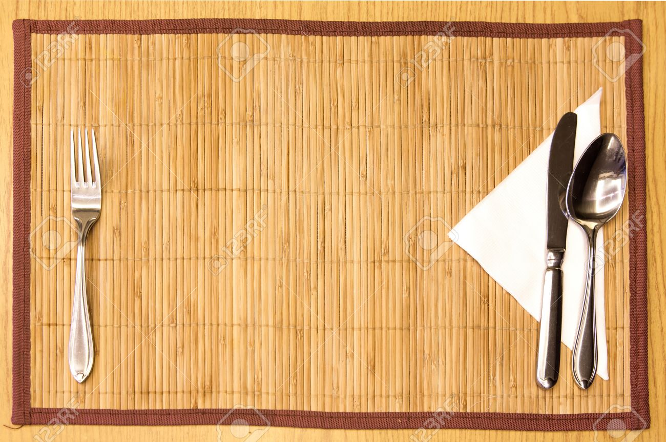 Table appointments- fork,knife,spoon, silk napkin on  bamboo mat Stock Photo - 14238394