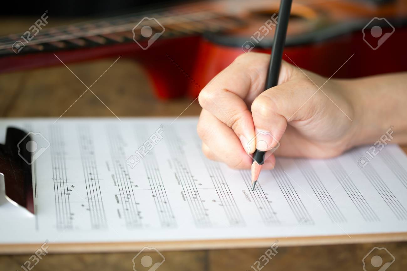 Hand with pencil and music sheet Stock Photo - 14448322
