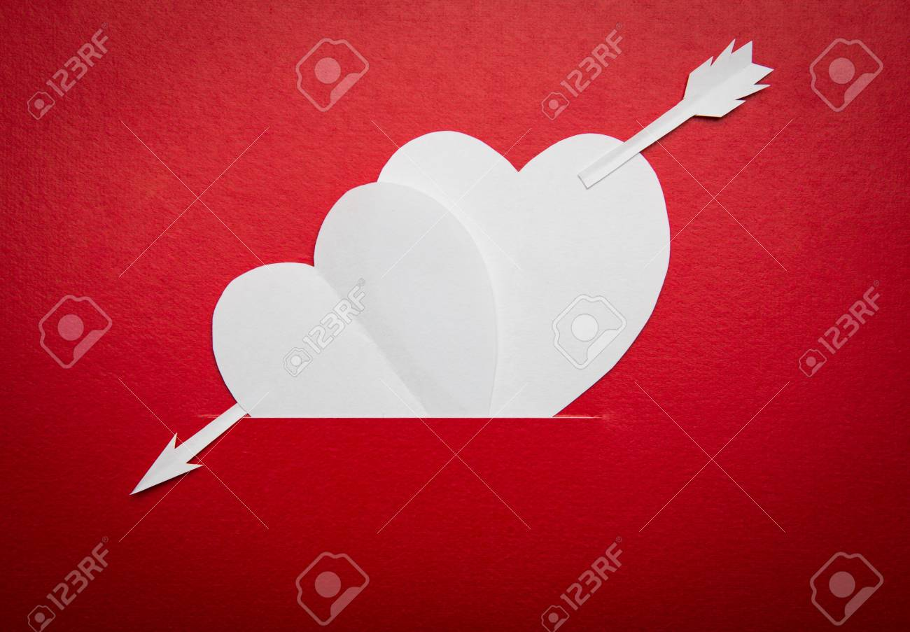 Two paper hearts pierced with an arrow symbol for Valentines day  with copy space for text or design Stock Photo - 16833284