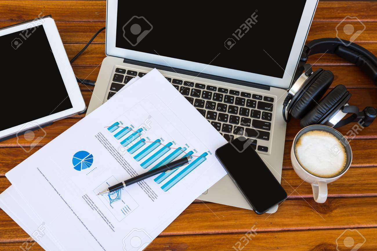 Laptop, tablet , smartphone and coffee cup with financial documents on wooden table Stock Photo - 30966207