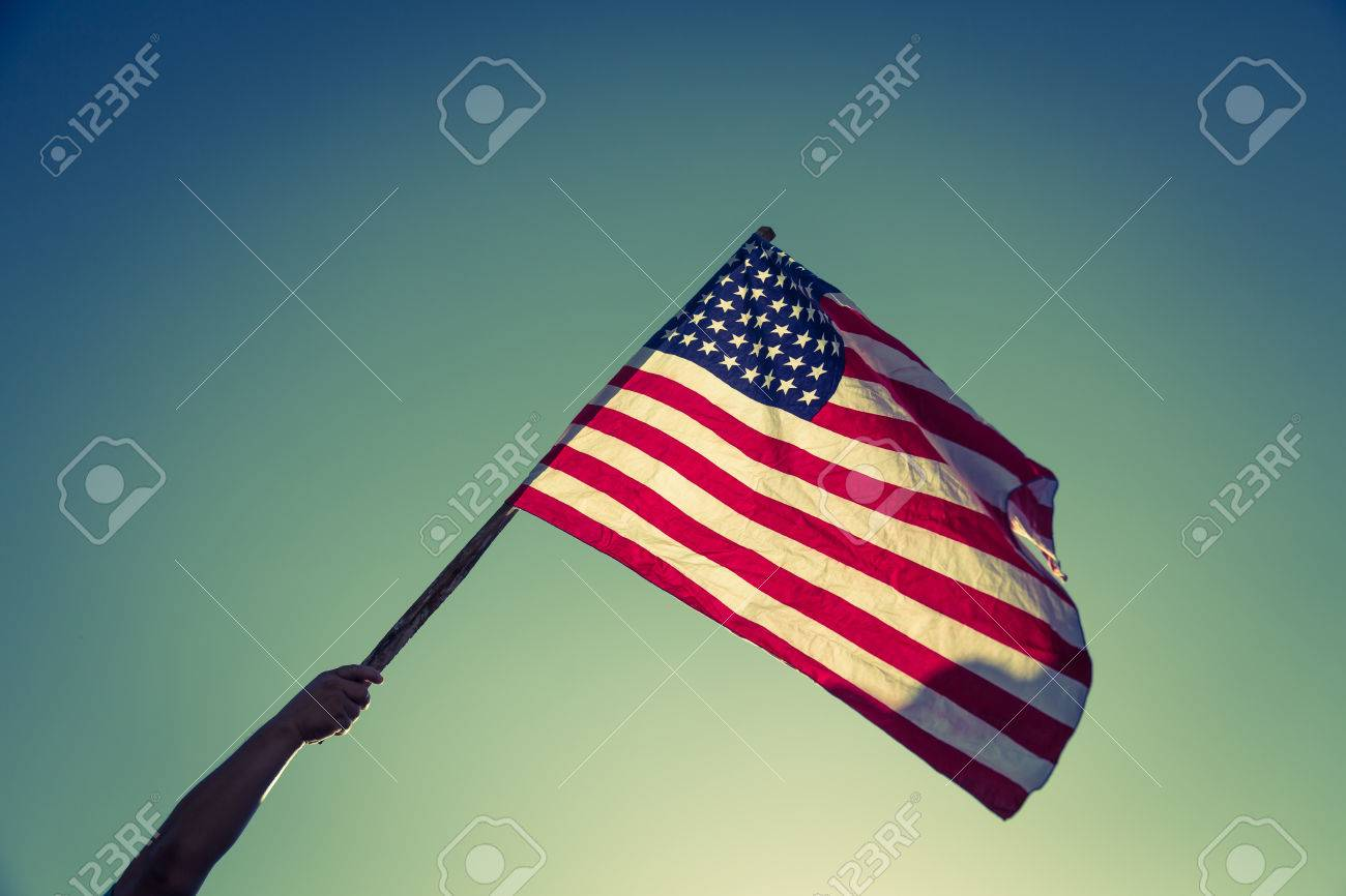 American flag with stars and stripes hold with hands against blue sky ( Filtered image processed vintage effect. ) - 42456723