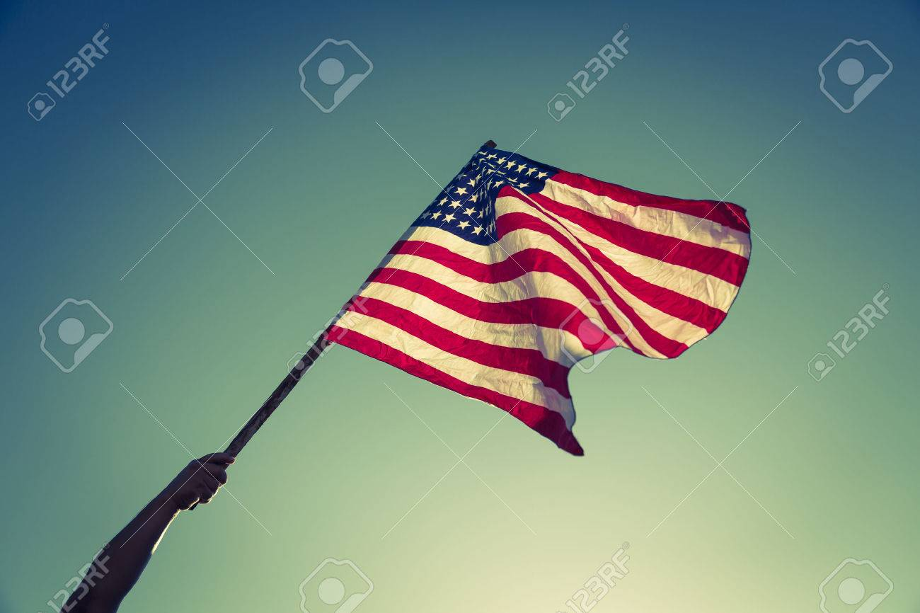 American flag with stars and stripes hold with hands against blue sky ( Filtered image processed vintage effect. ) - 42940516