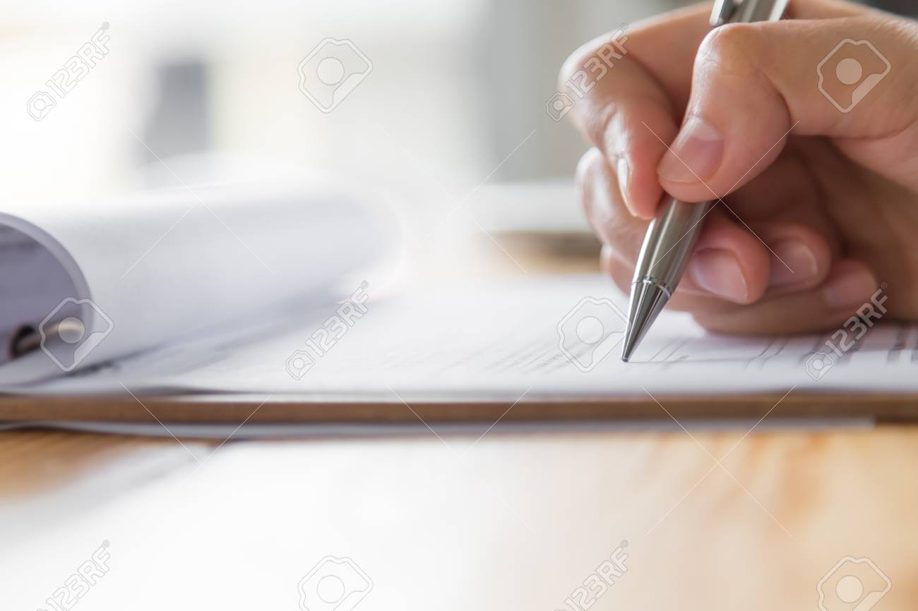 Hand with pen over application form - 46482443