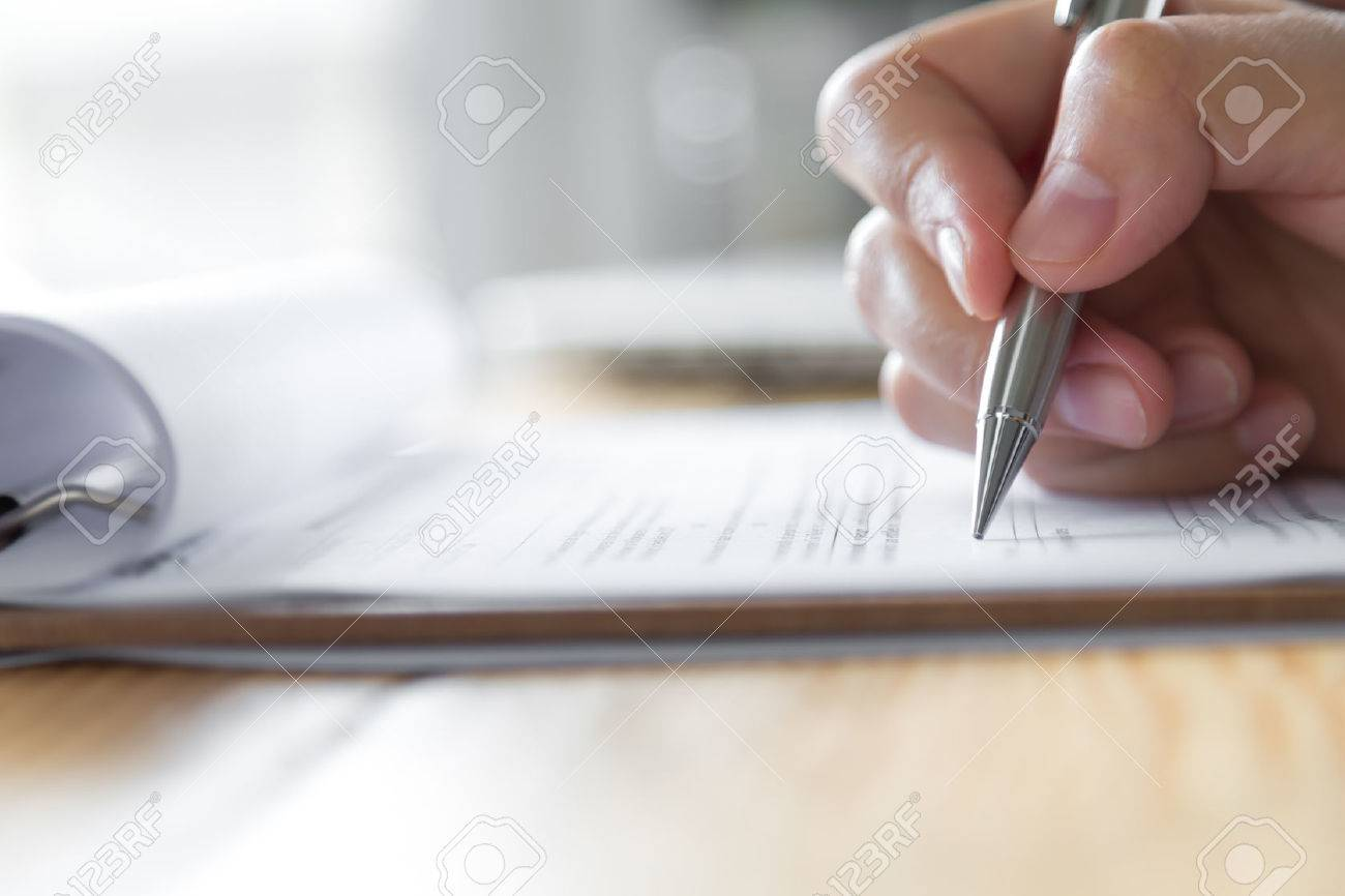 Hand with pen over application form - 47381804