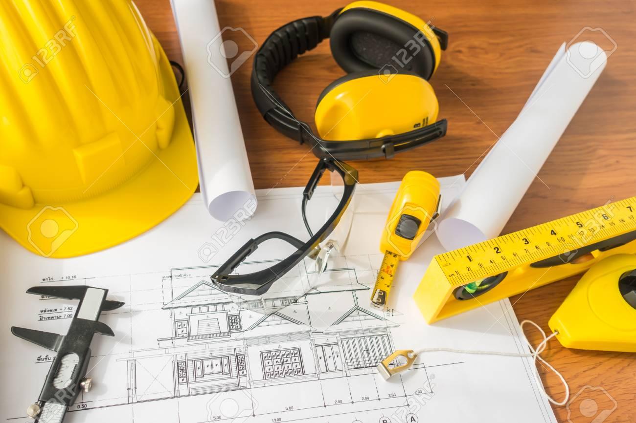 a73d6255a Los planes de construcción con casco amarillo y herramientas de dibujo de  planos