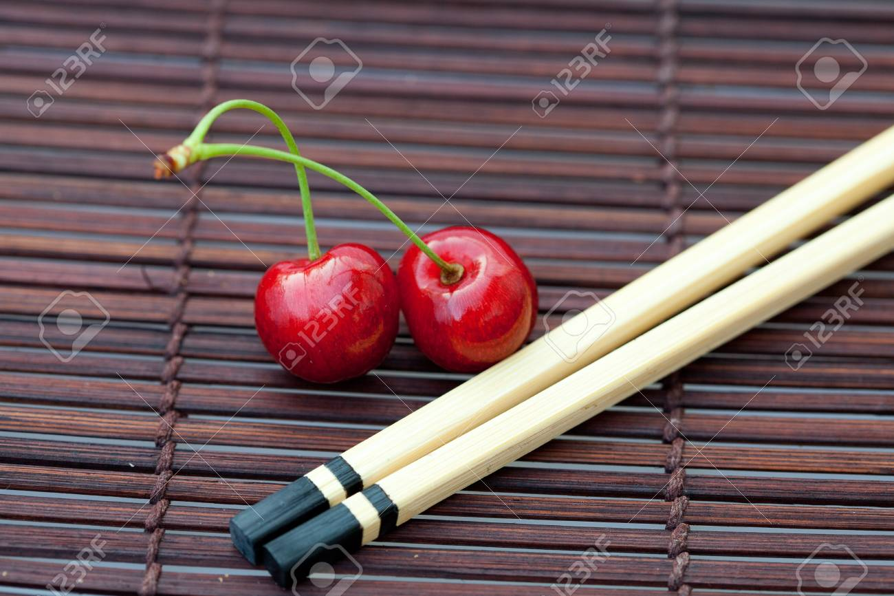 cherry and chopsticks on bamboo mat Stock Photo - 7716949