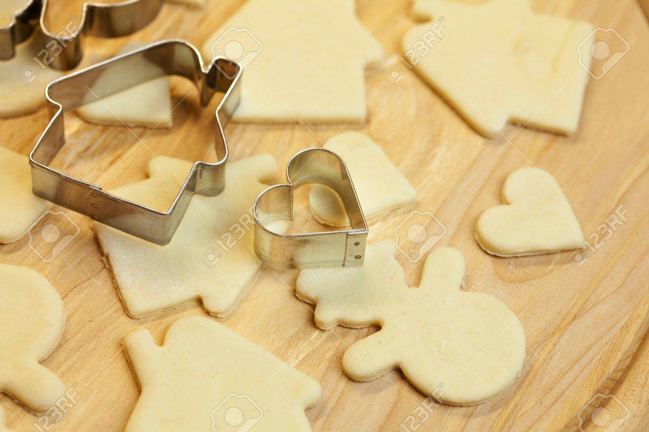 cut dough snowman, house, heart, and forms for cookies - 8299044