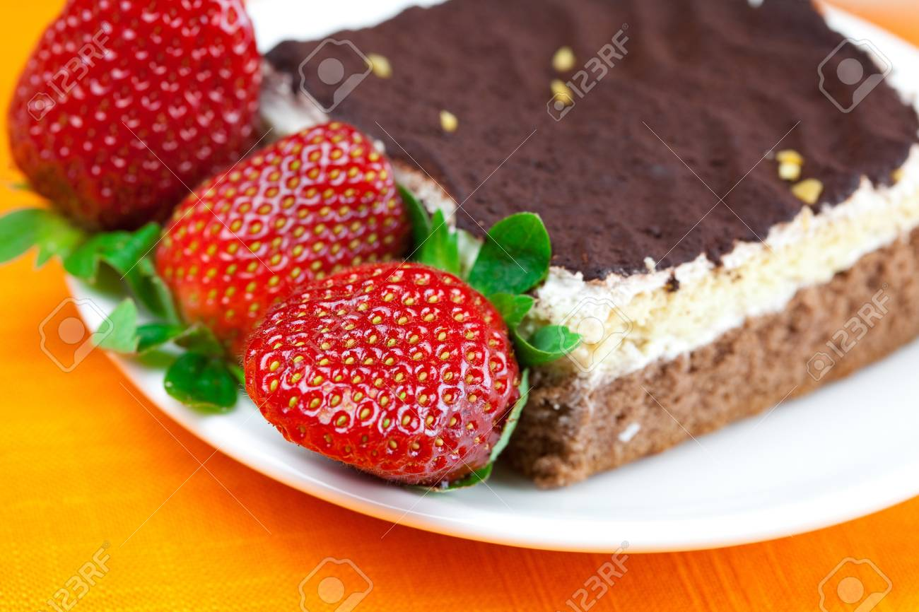 cake on a plate and strawberries lying on the orange fabric Stock Photo - 8672127