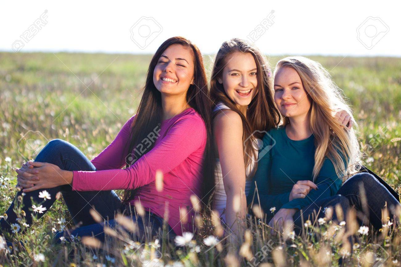 three young beautiful woman sitting in a field on the sky background - 9469929