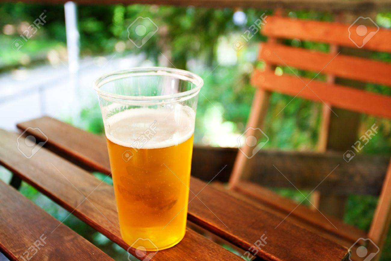 glass of beer standing on a wooden table - 9737432