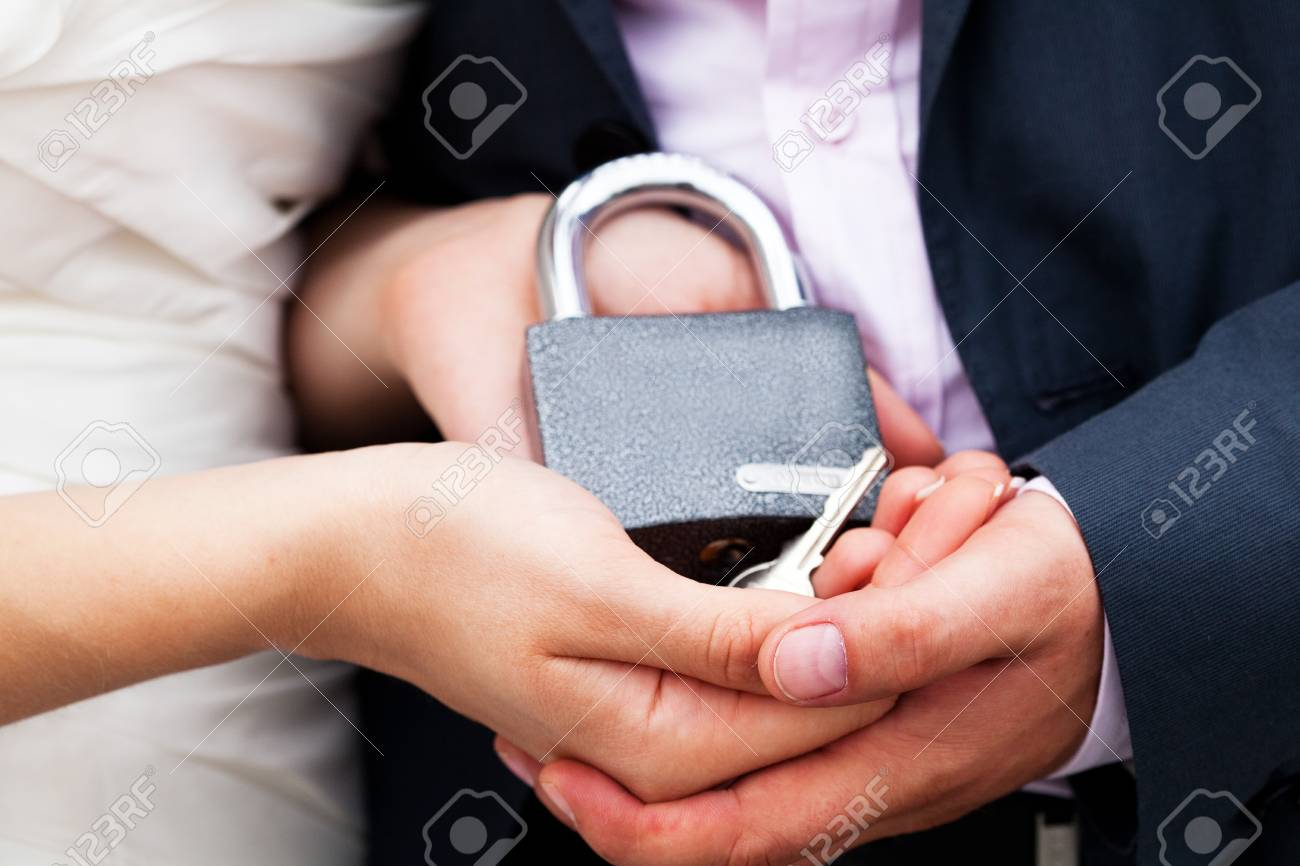 padlock with the chain in the hands of just married Stock Photo - 9737604