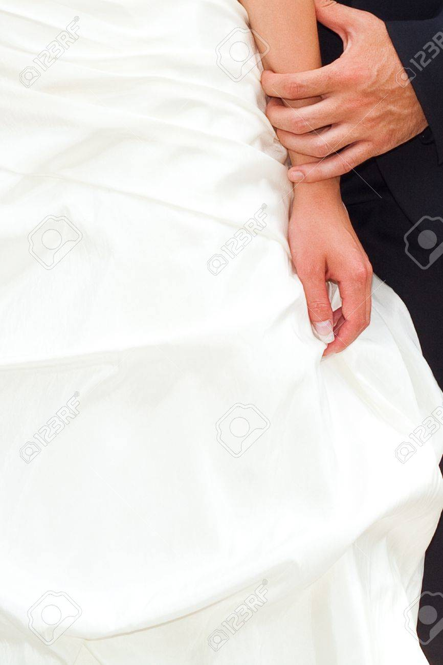 hands of the bride and groom on the background of a wedding dress - 9995719