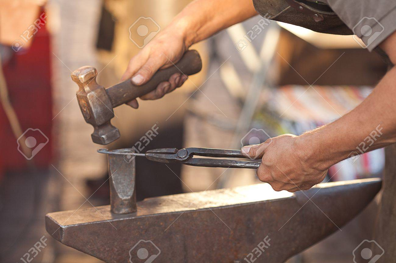 hammer, anvil and the hands of a blacksmith - 10694610