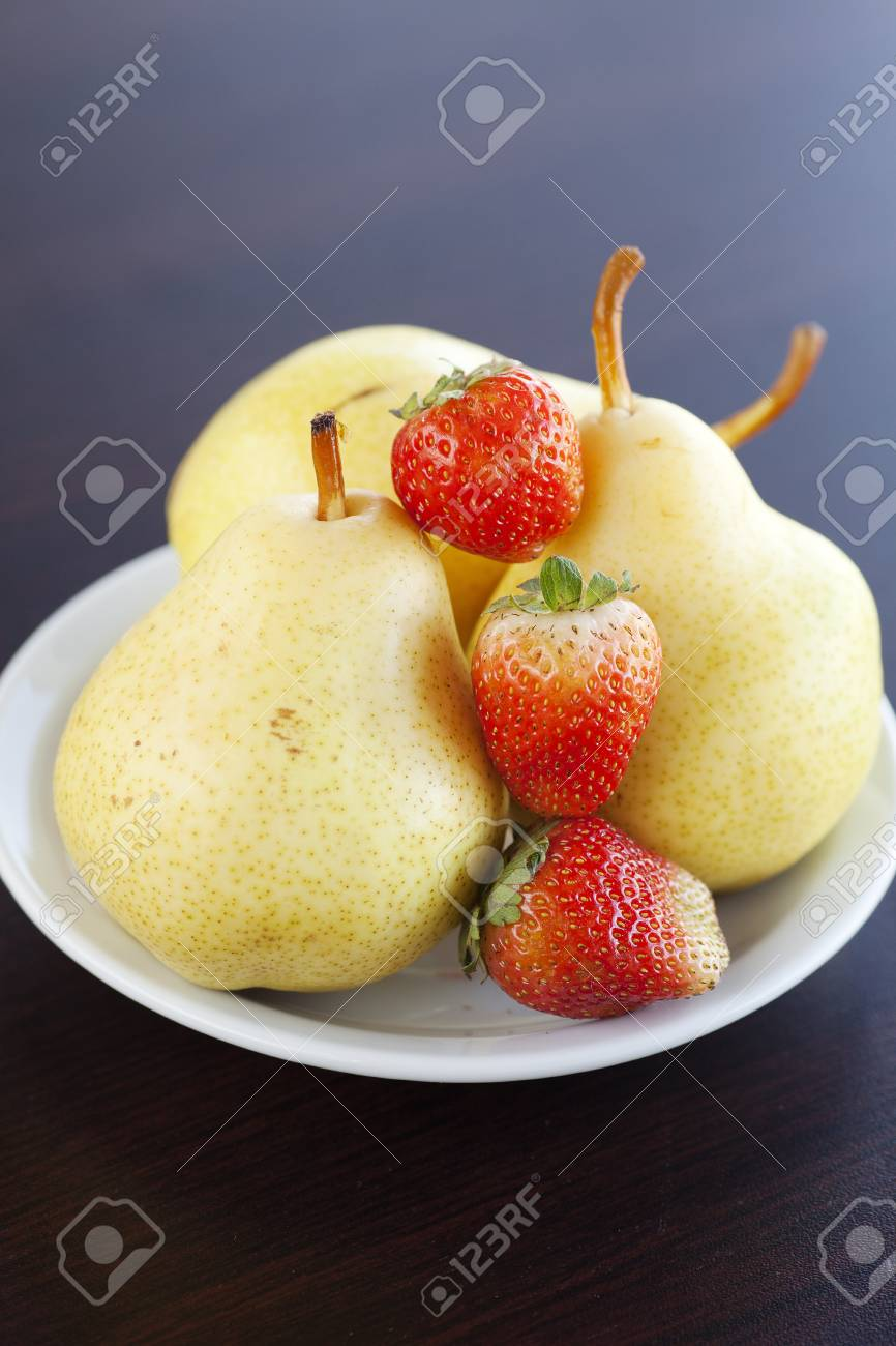 strawberries and  pears on a plate on a wooden table Stock Photo - 12711832