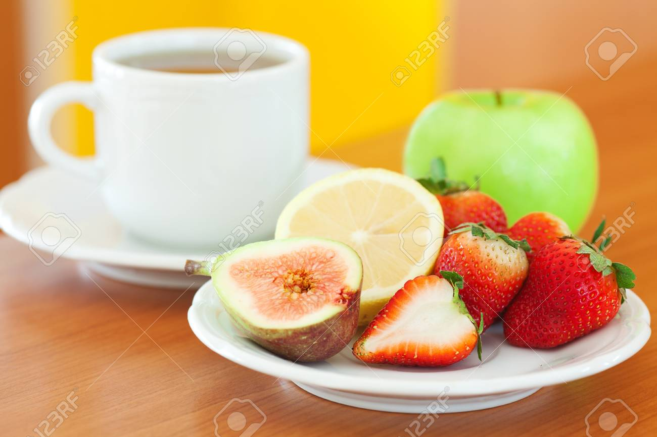 cup of tea, apple, lemon, fig and strawberries on a plate Stock Photo - 13640858
