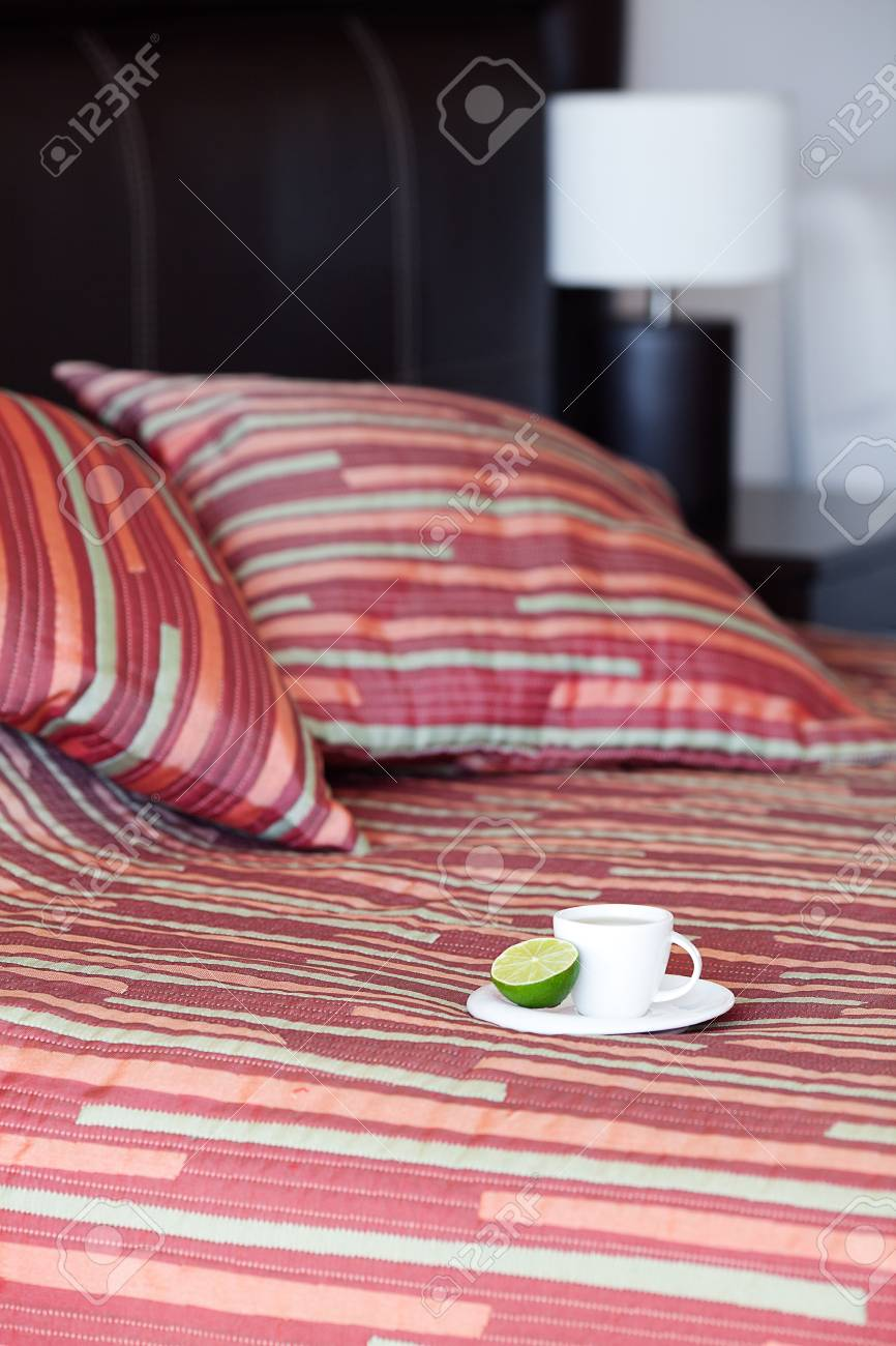bed with a pillow, a cup of tea on the bedside table and lamp Stock Photo - 13710552