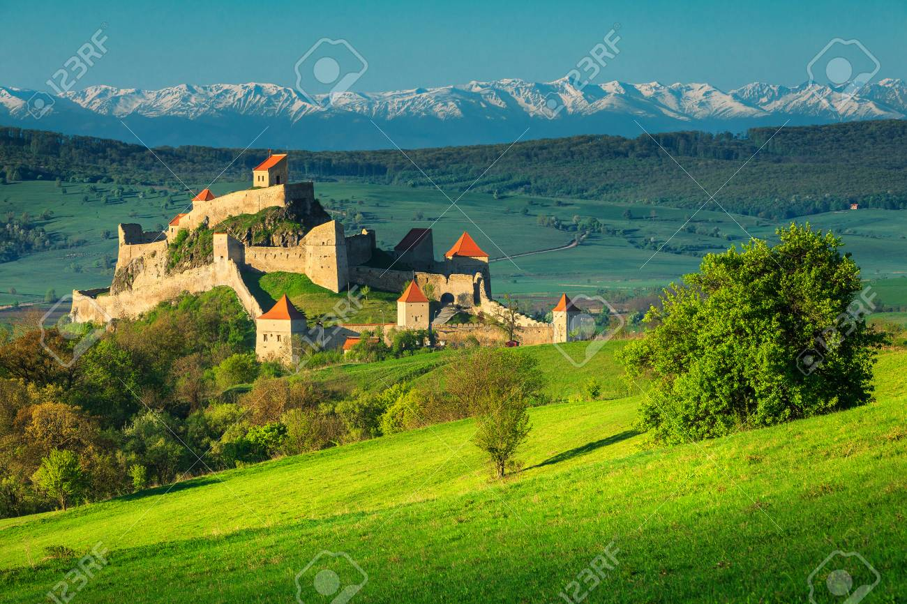 Famous Rupea fortress, spectacular fortification and high snowy mountains in background, Brasov, Transylvania, Romania, Europe - 100730316
