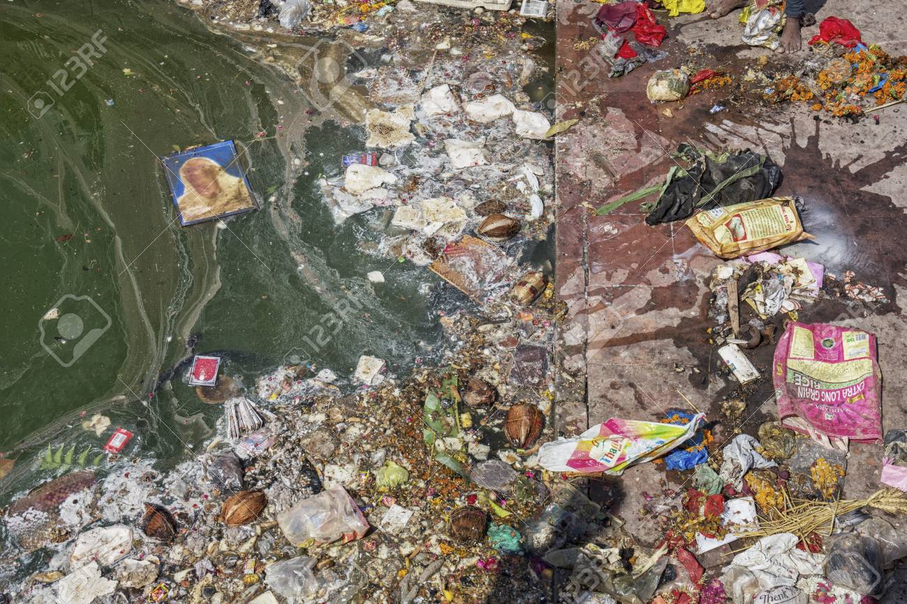 Pollution on a river. Plastic garbage, foam, wood and dirty waste on a river shore - 105390251