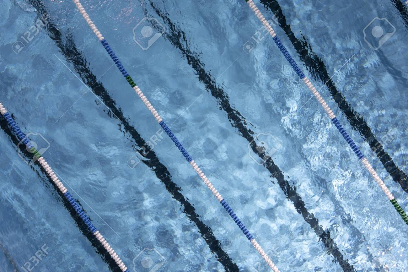Water ripples on blue tiled swimming pool background. View from..