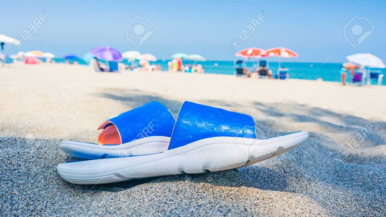 93be807d6701 relax time on spanish beach with sandals laying on the sand in the shadow  Stock Photo