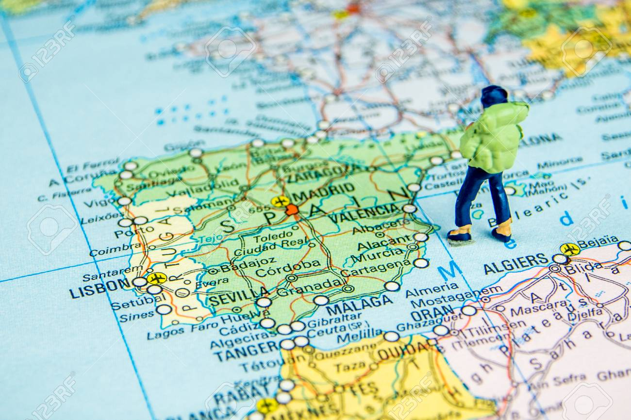 Big Map Of Spain.Closeup Of Miniature Figurine Of Young Traveller Standing On
