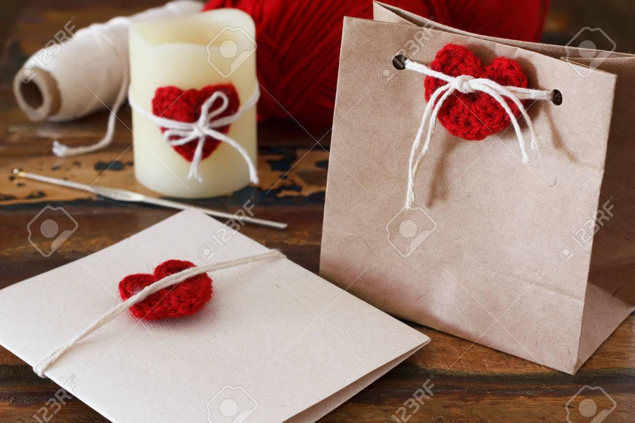 Decoration De Paquets Cadeaux saint-valentin décoration: main crochet coeur rouge pour la carte de voeux,  paquet cadeau et bougie. mise au point sélective