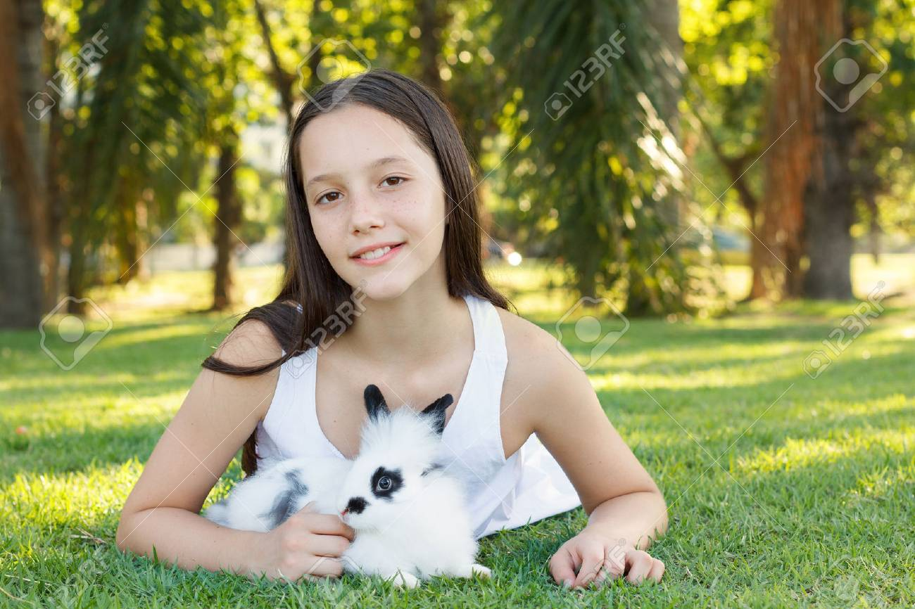 Cute beautiful smiling teen girl on grass with white and black baby rabbit.  Selective focus