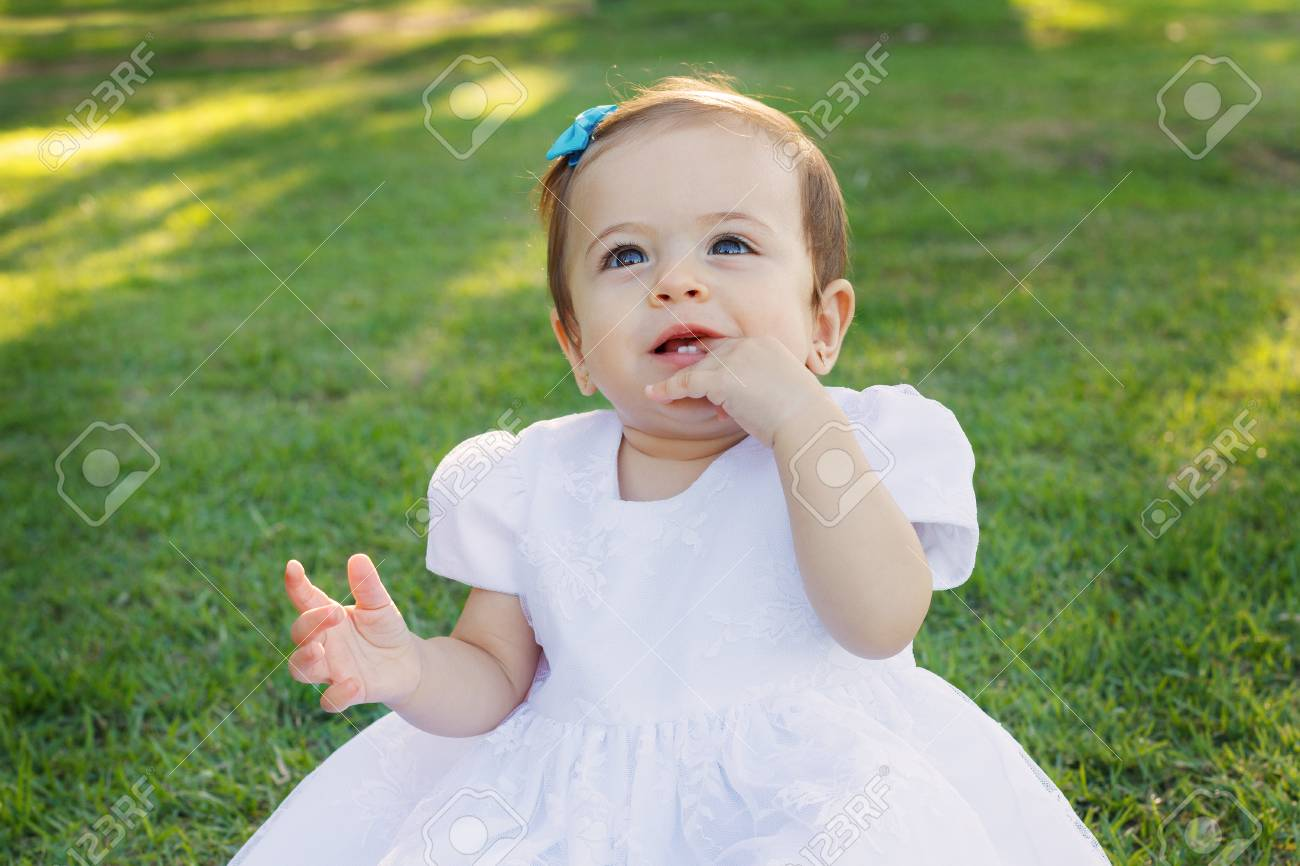 4bbb5f568 Cute Happy Smiling Little Baby Girl In White Dress Scratching ...