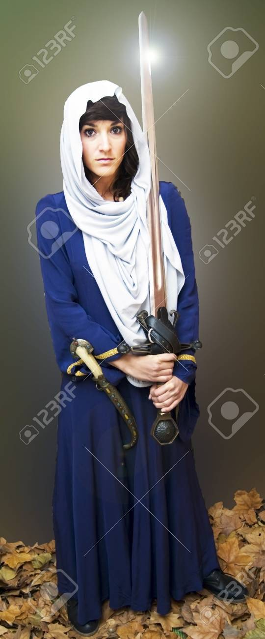 Portrait of a beautiful medieval woman with a shining sword Stock Photo - 17471810