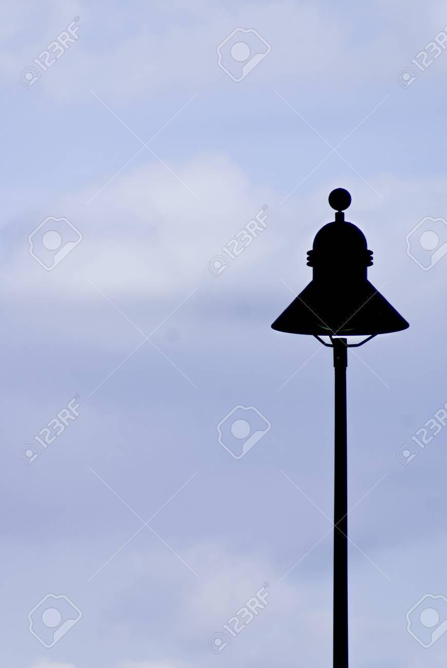 A street lamp silhouette againt a slightly overcast blue sky. Stock Photo - 10401610