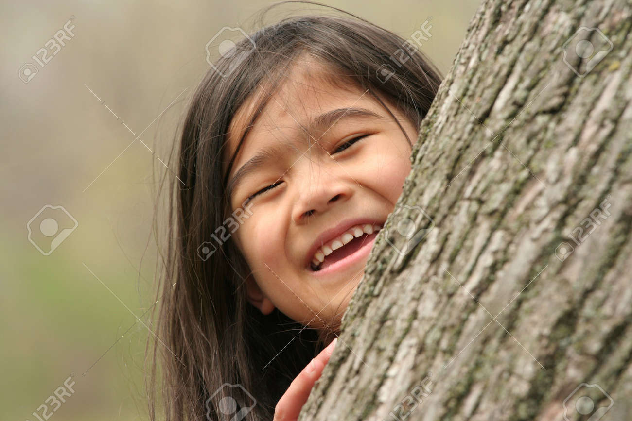 Little girl peeking out from behind a tree Stock Photo - 3089625