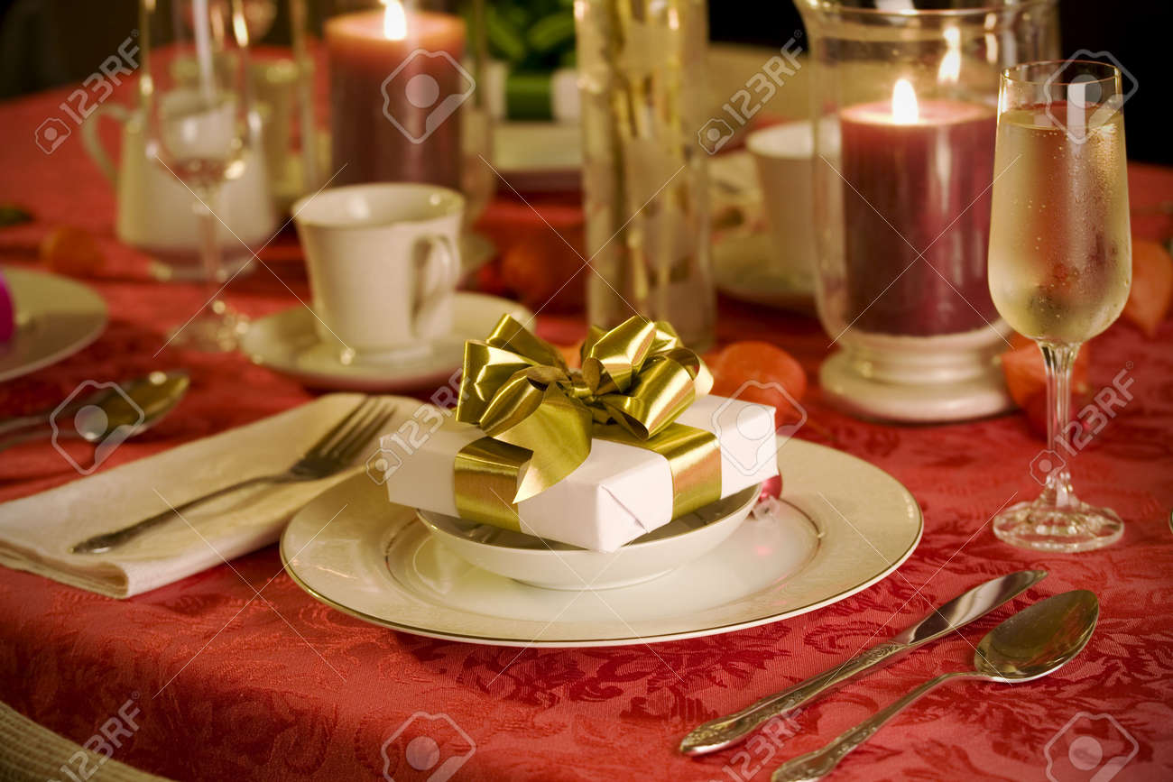 Elegant christmas table decorations - Stock Photo Elegant Christmas Table Setting In Red With Gold Gift As Focal Point
