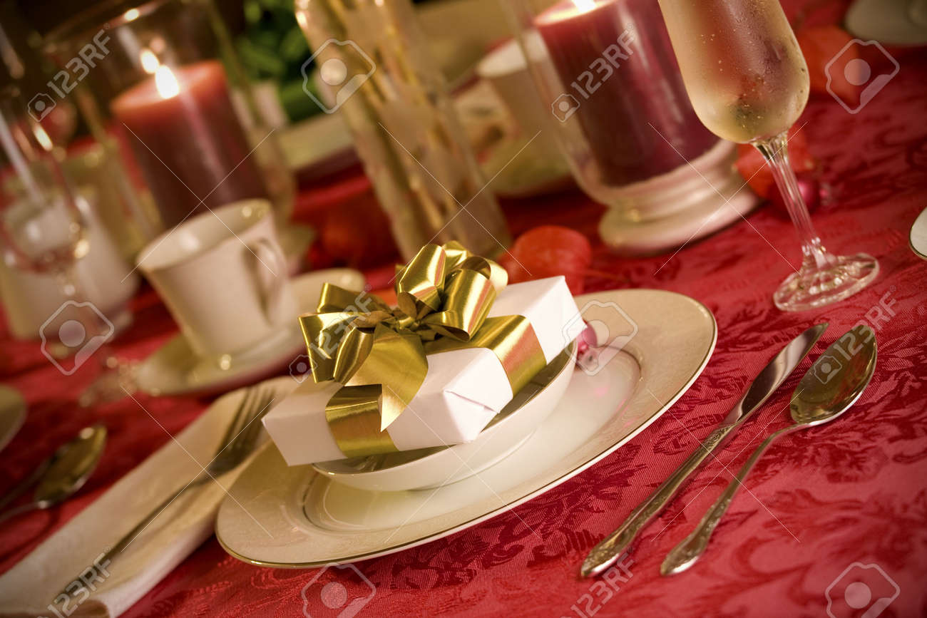 Gold christmas table setting - Elegant Christmas Table Setting In Red And Gold Colors Gift As Focal Point Stock Photo
