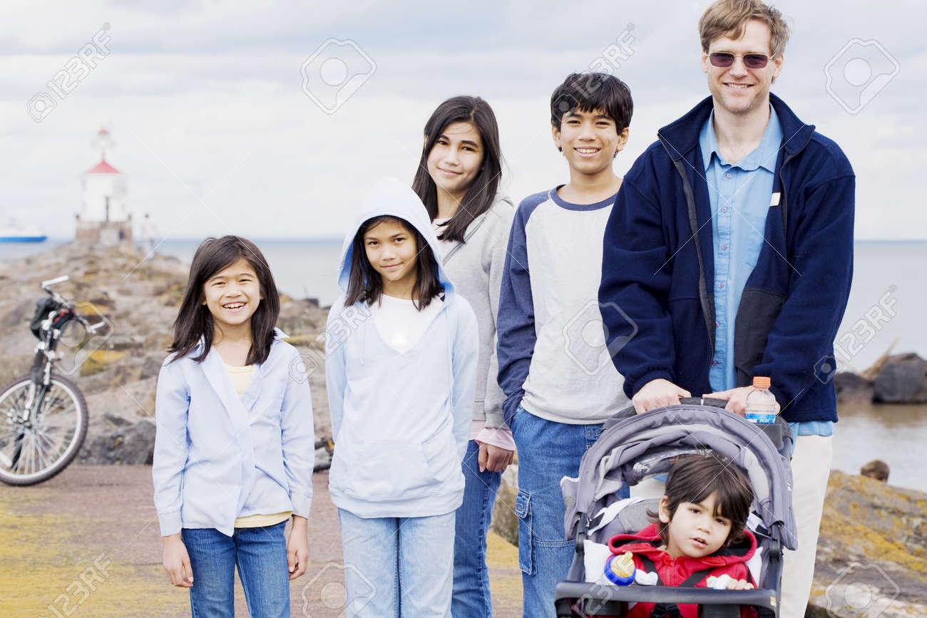 Interacial Stunning father with his five children at the beach, interracial family