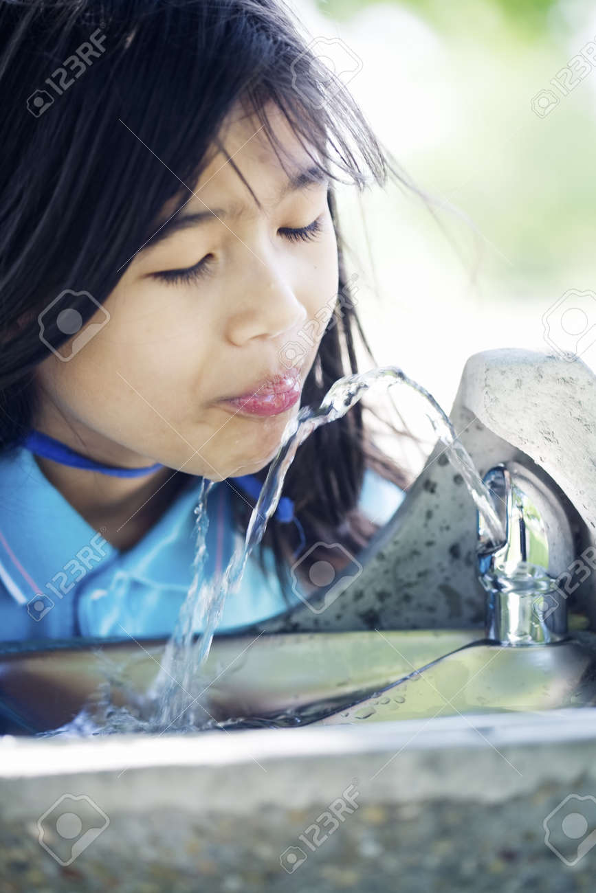 Girl drinking from water fountain Stock Photo - 9018592