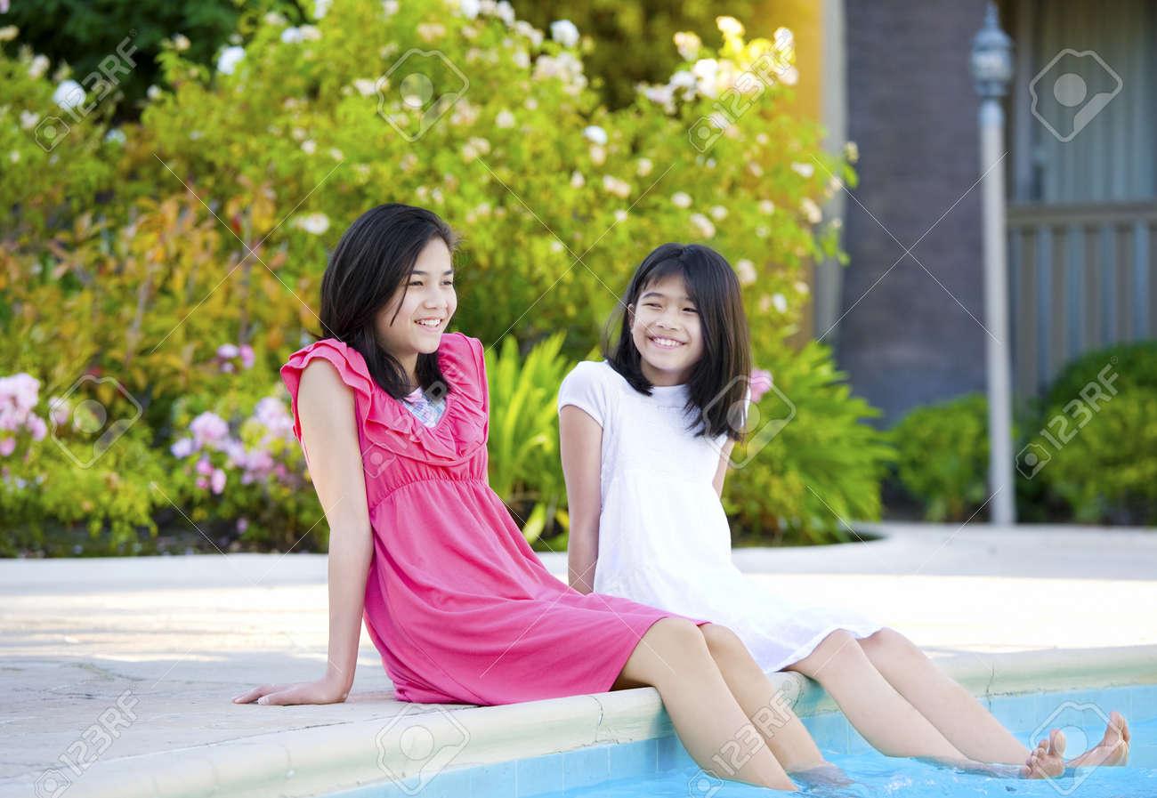 Two young girls, biracial, part- Asian, enjoying time sitting by pool. Stock Photo - 11254505