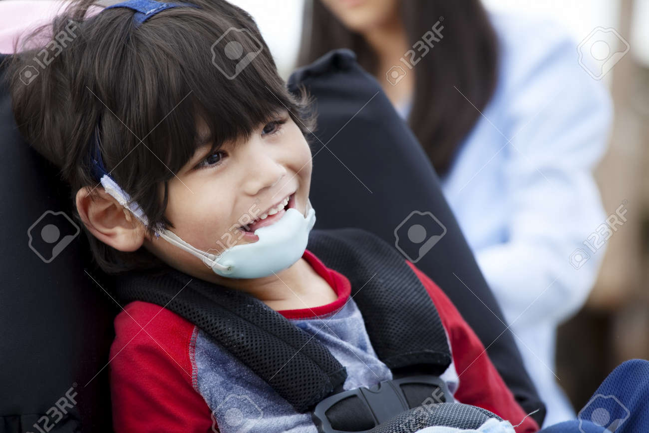 Happy five year old disabled boy in wheelchair and protective gear Stock Photo - 13562827