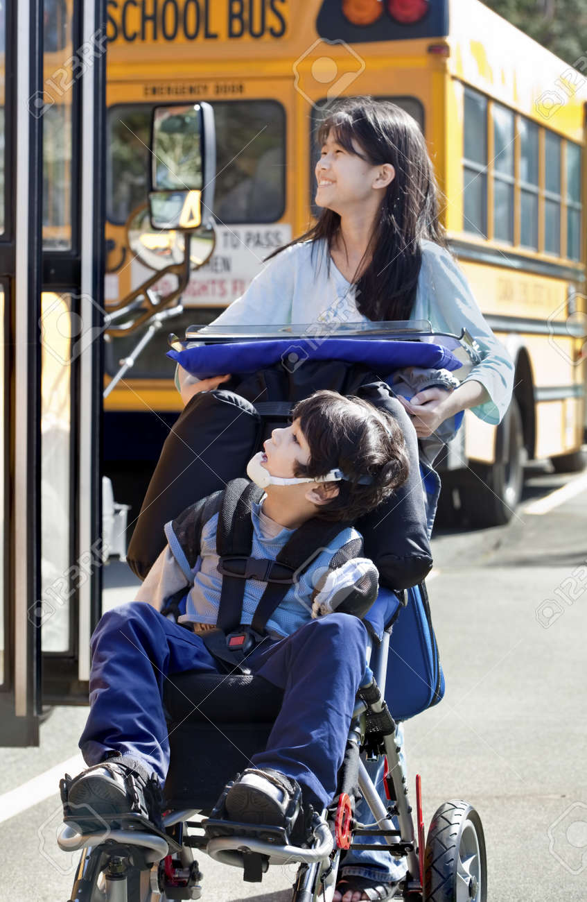 Ten year old girl  pushing disabled little boy wearing protective gear  in wheelchair  next to school bus. Child has cerebral palsy. Stock Photo - 15585140