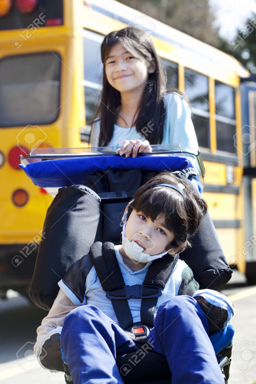 Ten year old girl  pushing disabled little boy wearing protective gear  in wheelchair  next to school bus. Child has cerebral palsy. Stock Photo - 15585135