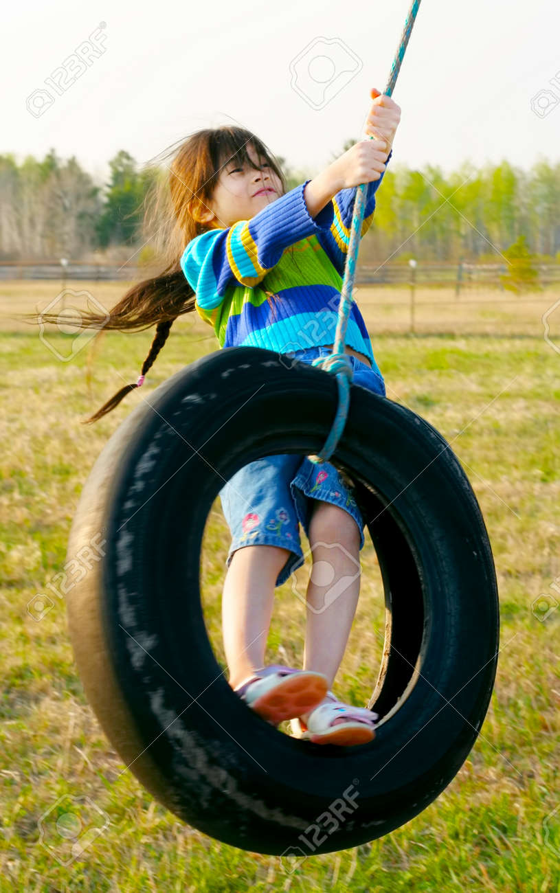 Little girl swinging on tire swing in the countryside Stock Photo - 17033511