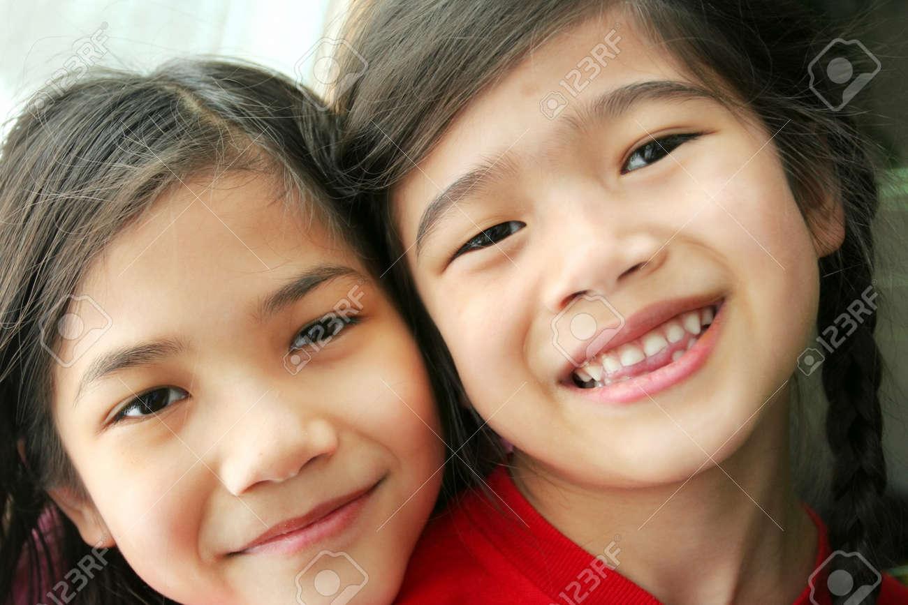 Two girls. Sisters. Part Scandinavian, part asian. Stock Photo - 17034275