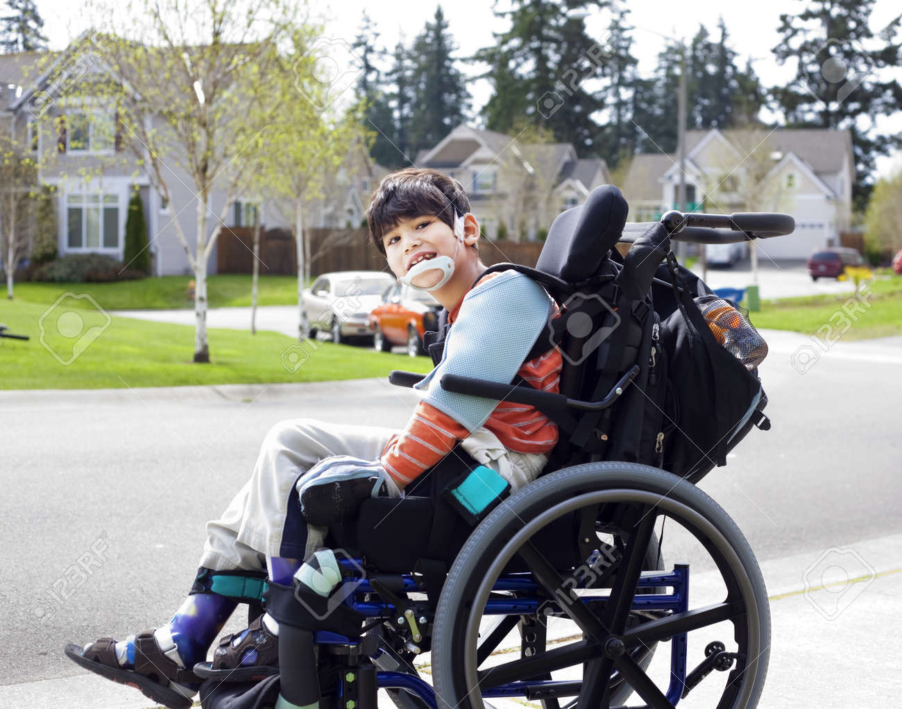 happy disabled six year old boy waiting on sidewalk in wheelchair