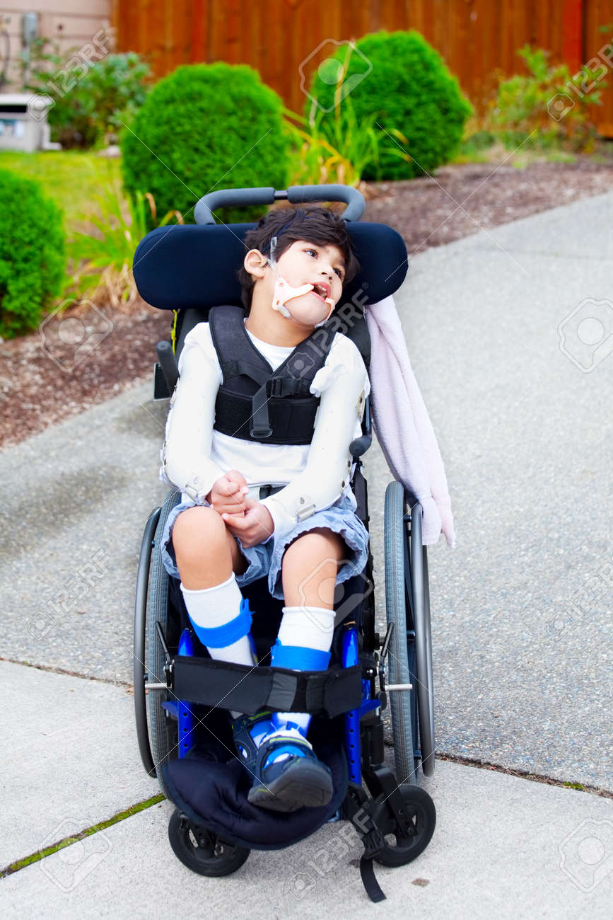 Seven year old biracial disabled boy in wheelchair. Child has cerebral palsy. - 23378763