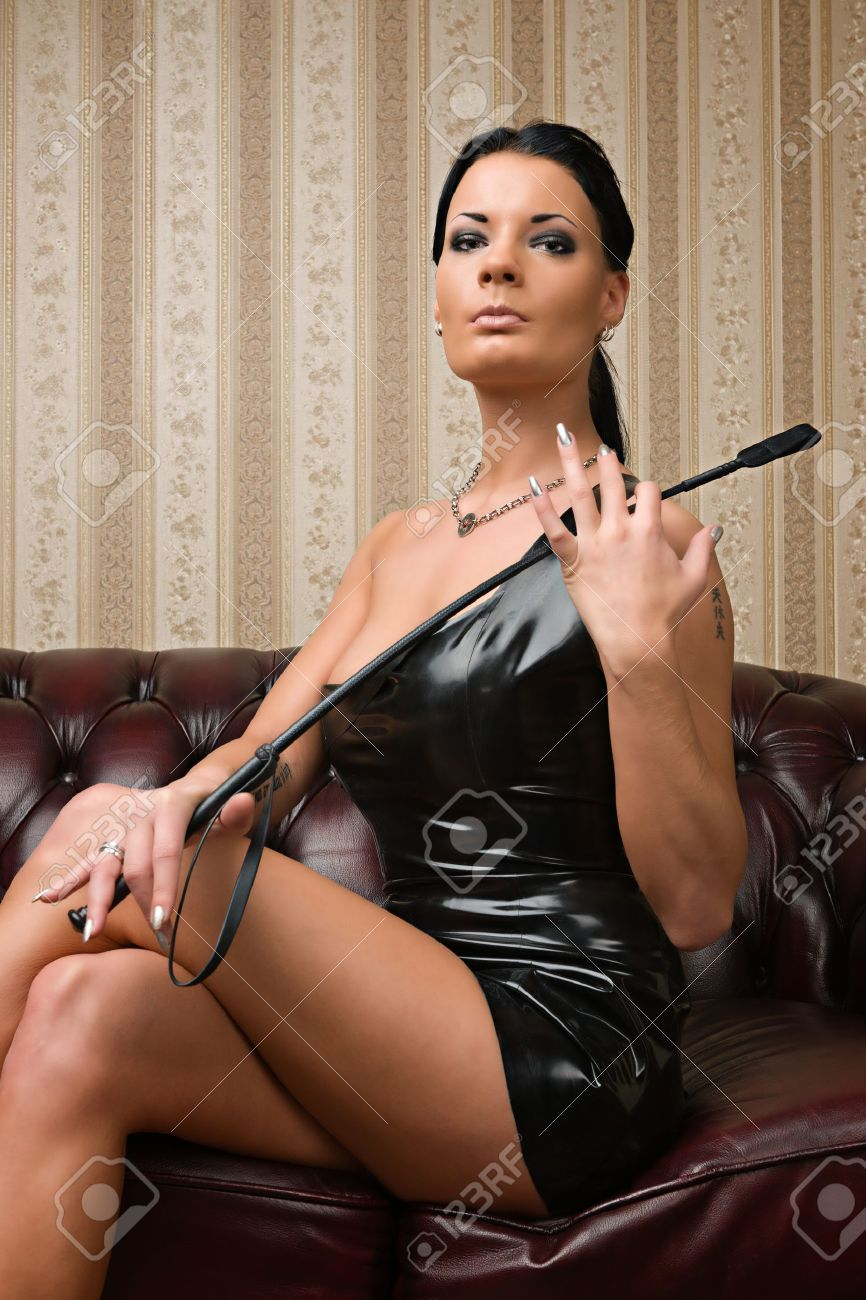 A young brunette lady mistress and leather couch on background Stock Photo - 12499138