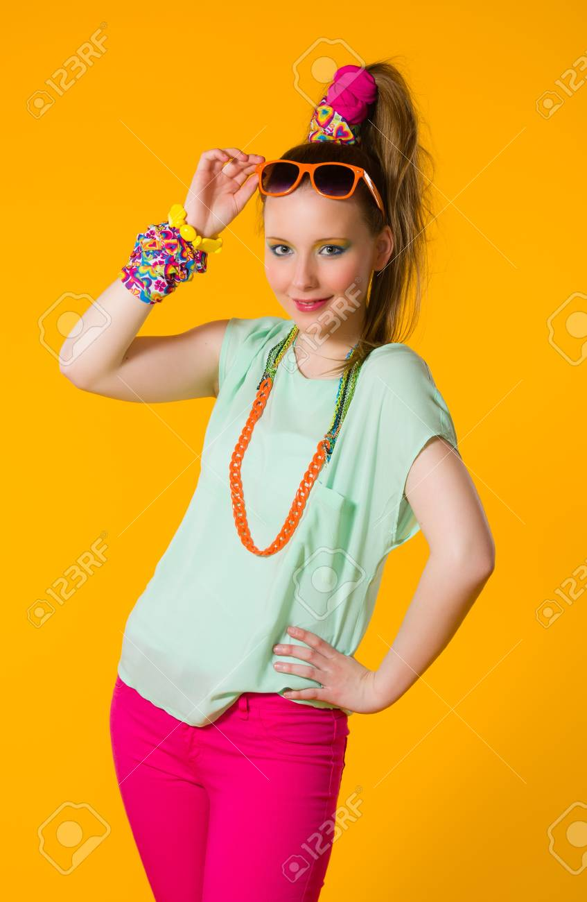 Happy girl with colorful clothes, yellow background Stock Photo - 20237011