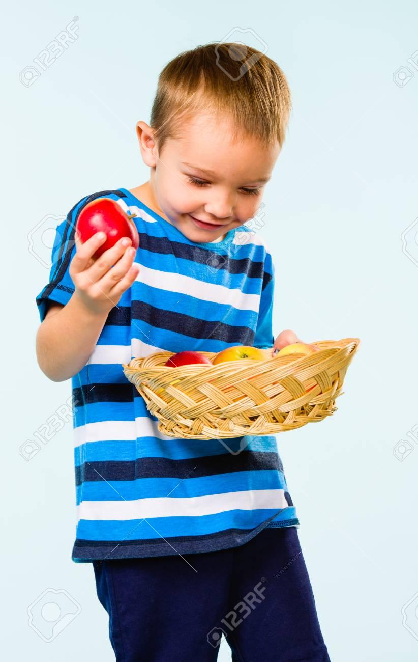 Little boy on striped t-shirt, fruit basket, studio shot and light blue background Stock Photo - 22442586