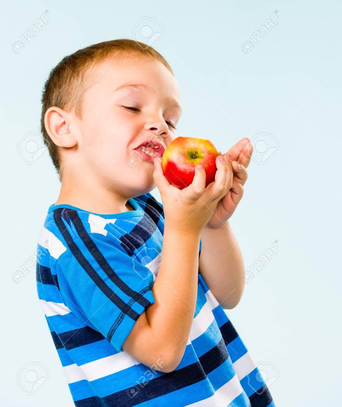 Little boy on striped t-shirt eating apple, studio shot and light blue background Stock Photo - 22442592