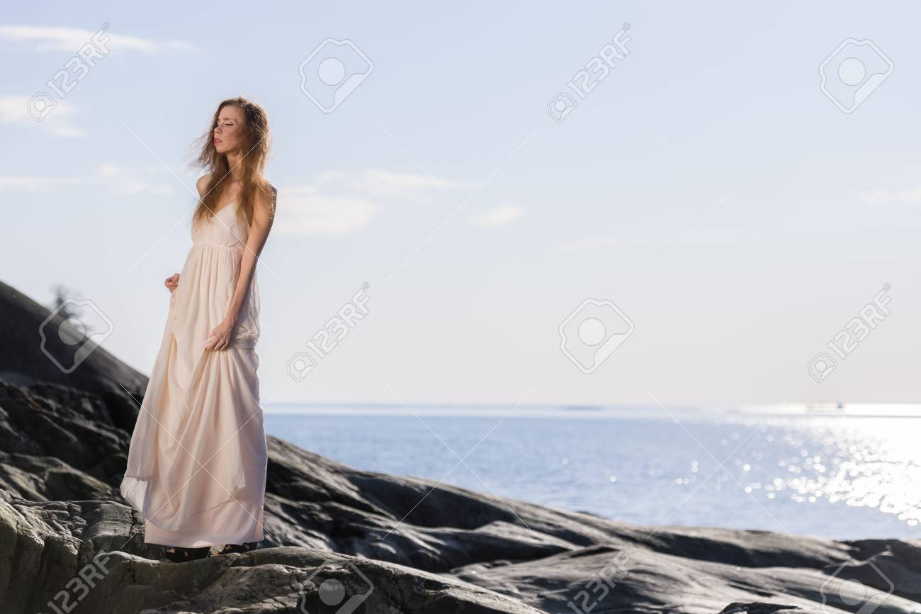 White dress by the shore - Beautiful Young Woman Wearing White Dress Scandinavian Shore And Sea On Background Stock Photo