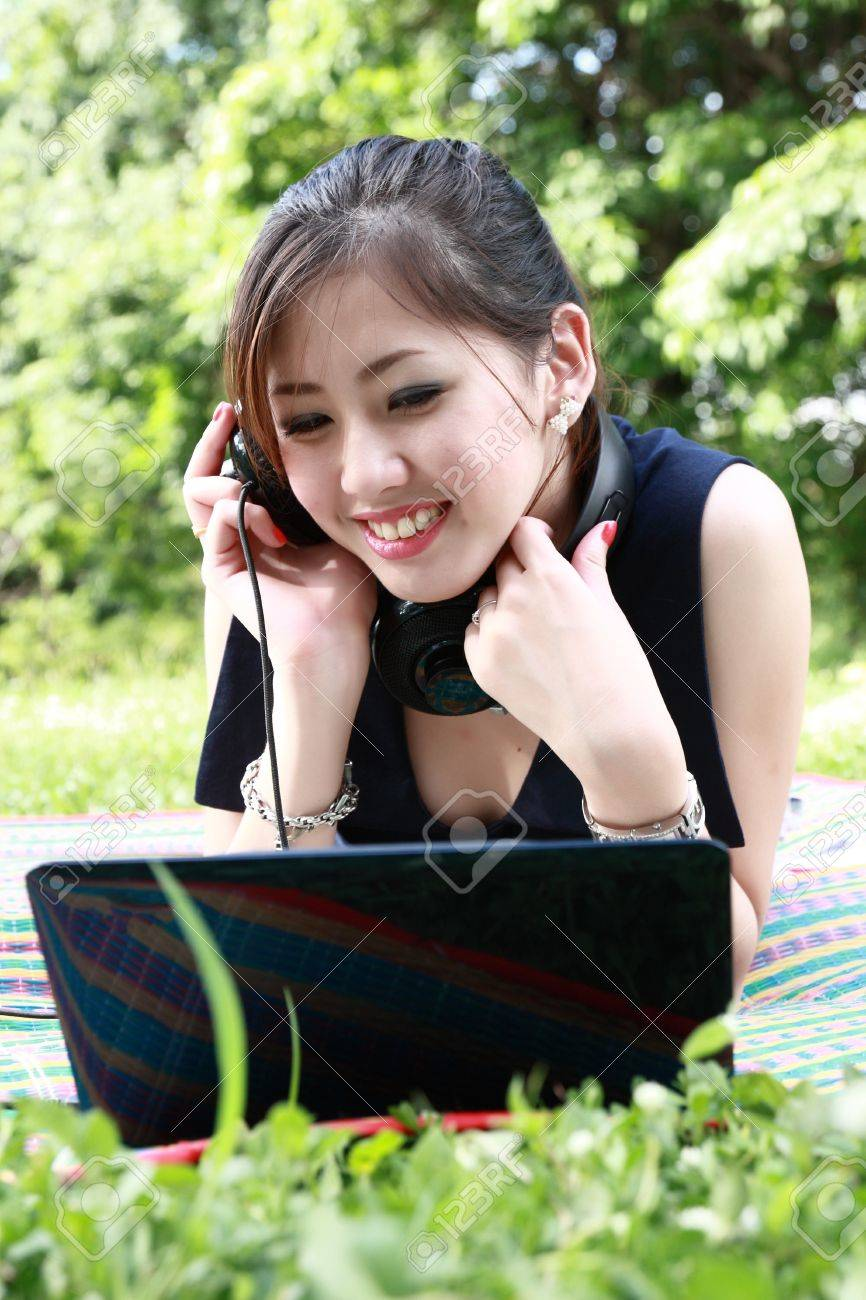 cute Girl with a laptop and headphones at the park